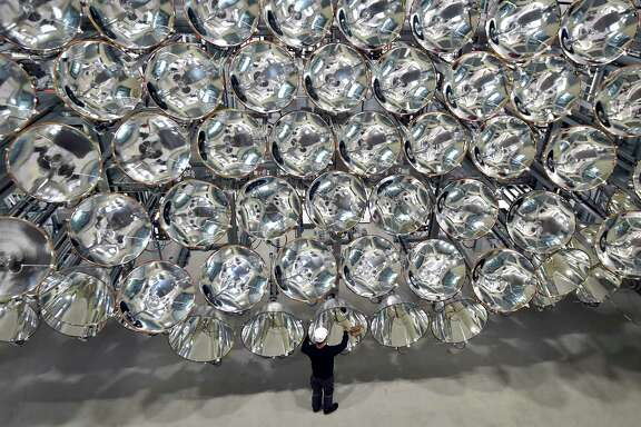 "An engineer stands in front of xenon short-arc lamps in Germany's DLR Institute for Solar Research. The lights are part of an ""artificial sun"" that will be used for research purposes."