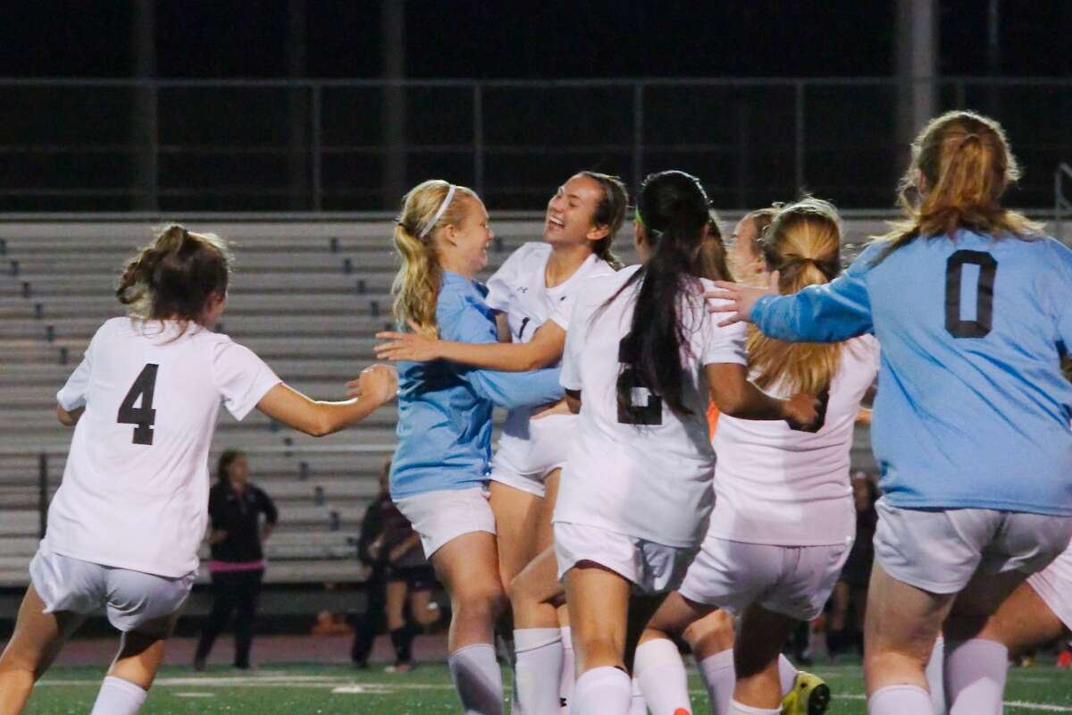 Clear Falls goalkeeper Maddy Anderson (1) gets a hug from Clear Falls Nina Zapalac (19) after Anderson scores the winning goal in a penalty kick shootout to secure the victory over Pearland Thursday, Mar. 23 at Friendswood High School.