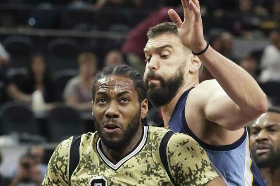 Kawhi Leonard braces as Marc Gasol moves in on his back as the Spurs host the Grizzlies at the AT&T Center on March 23, 2017.