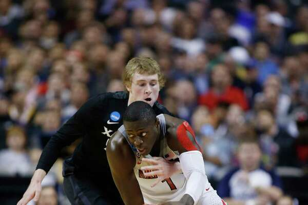 Xavier guard J.P. Macura, left, defends on Arizona guard Rawle Alkins (1) during the first half of an NCAA Tournament college basketball regional semifinal game Thursday, March 23, 2017, in San Jose, Calif.