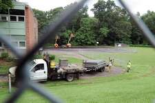 Workers from Total Fence Co. install fencing around the fields at Western Middle School in the Byram section of Greenwich, Conn., Thursday, Sept. 1, 2016. The fields have been closed by town officials after tests found elevated levels of lead and other toxins in the soil there.
