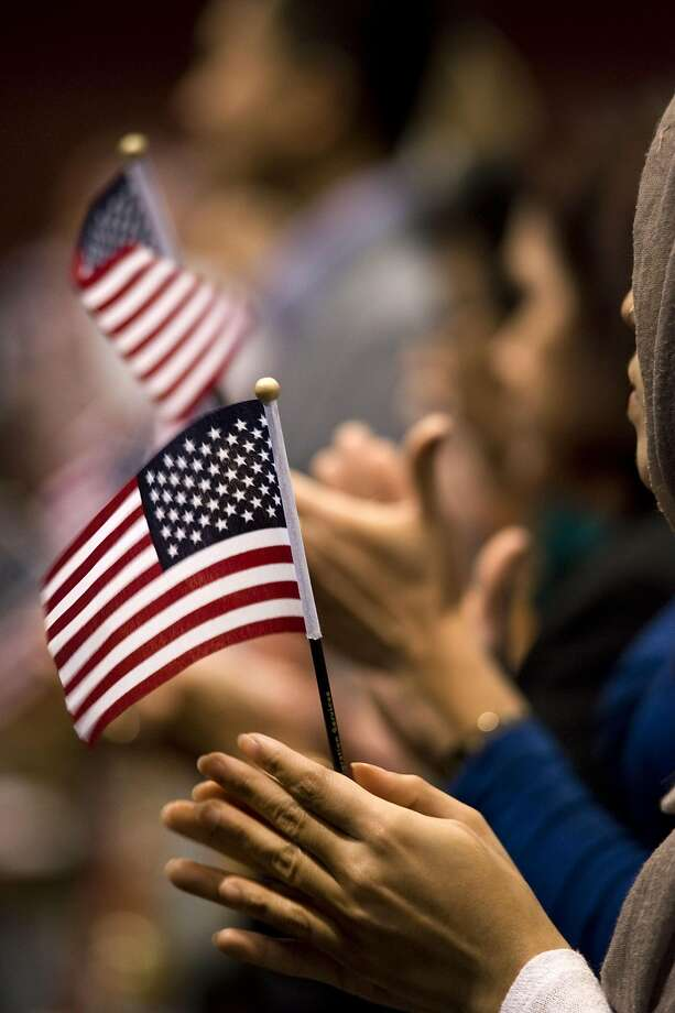 A woman holds an American flag during a naturalization ceremony in San Diego on Wednesday. Photo: David Maung, Bloomberg