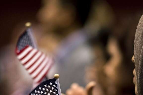 "A woman holds a miniature American flag during a naturalization ceremony in San Diego, California, U.S., on Wednesday, March 22, 2017. Hawaii's attorney general is seeking to extend a temporary restraining order blocking Donald Trump's revised travel ban, citing the president's own words as evidence that the new policy is merely a ""subterfuge."" Photographer: David Maung/Bloomberg"