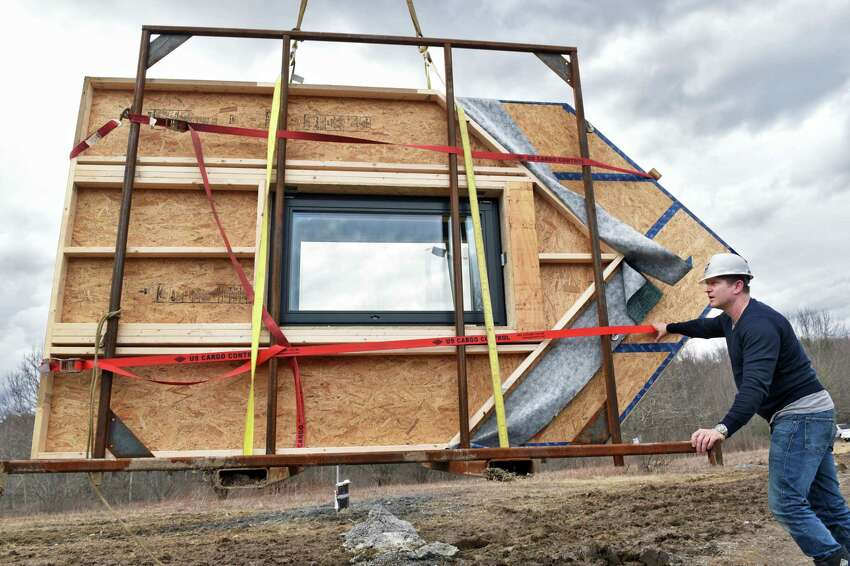 Founder and Technical Director of Ecocor, Chris Corson guides prefabricated gables into position as they construct a house featuring a passive solar design Wednesday March 1, 2017 in Altamont, NY. (John Carl D'Annibale / Times Union)