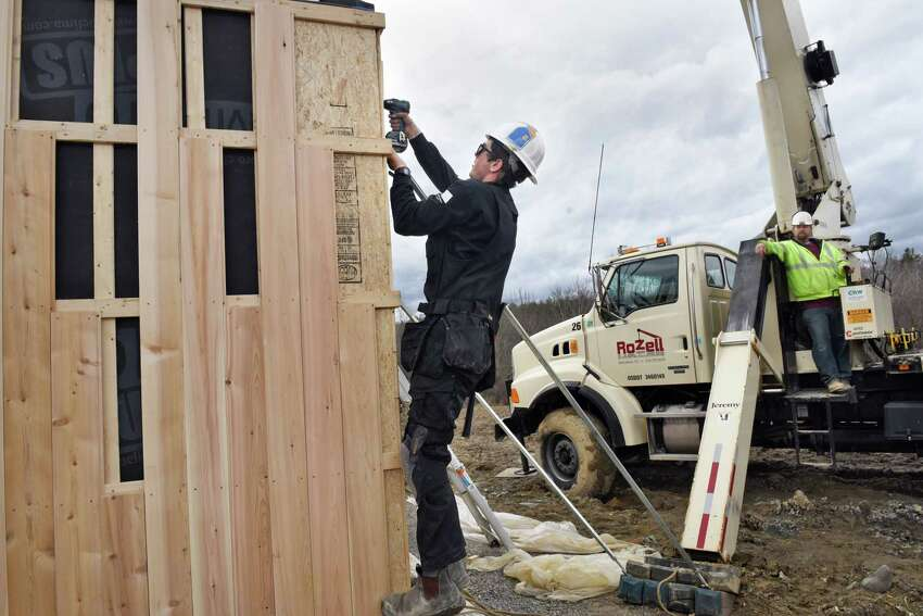 Project manager George Reefer, center, secures the final wall section as they construct a house featuring a passive solar design Wednesday March 1, 2017 in Altamont, NY. (John Carl D'Annibale / Times Union)