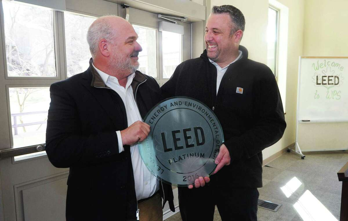 Winston Preparatory School Executive Director Scott Bezsylko accepts a LEED (Leadership in Energy and Environmental Design) Platinum certification for environmental architecture/engineering of its building from Sandpebble Operations Manager Chris Barletta during a brief ceremony Thursday, March 23, 2017, in Norwalk, Conn.