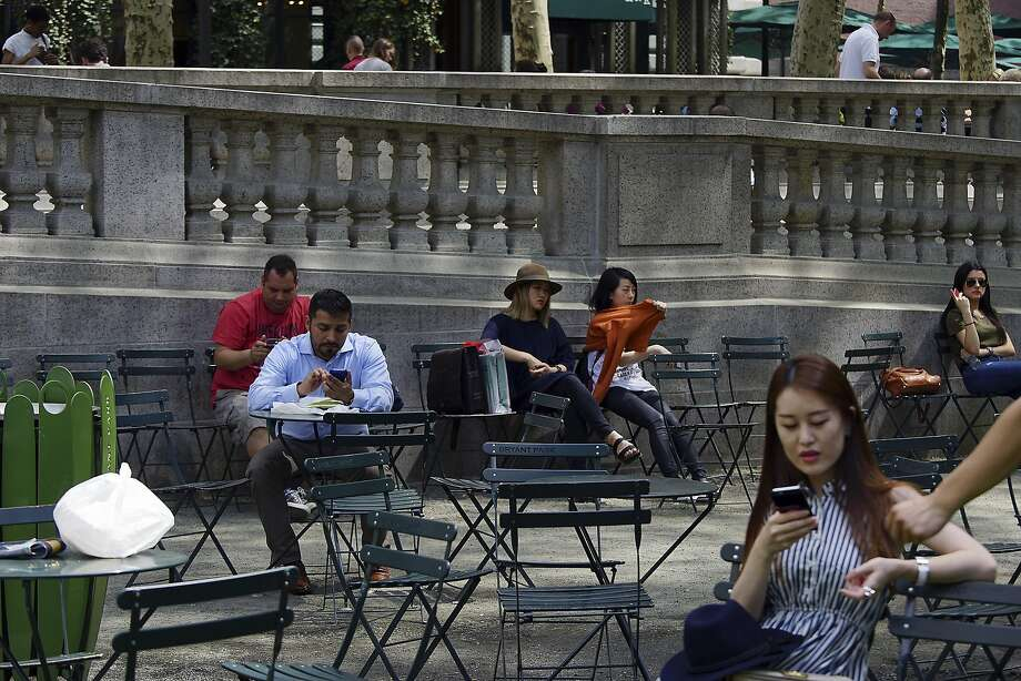 FILE — Visitors on their phones in Bryant Park in Manhattan, May 12, 2015. The Senate voted to overturn regulations that required telecom companies to ask permission before tracking users' behavior, beginning a repeal of Obama-era regulations. (Todd Heisler/The New York Times) Photo: TODD HEISLER, NYT