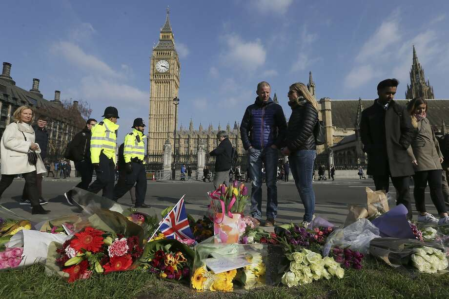 Mourners pass tributes to the victims of Wednesday's attack near the Houses of Parliament in London. A 52-year-old Briton is suspected in the rampage. Photo: Tim Ireland, Associated Press
