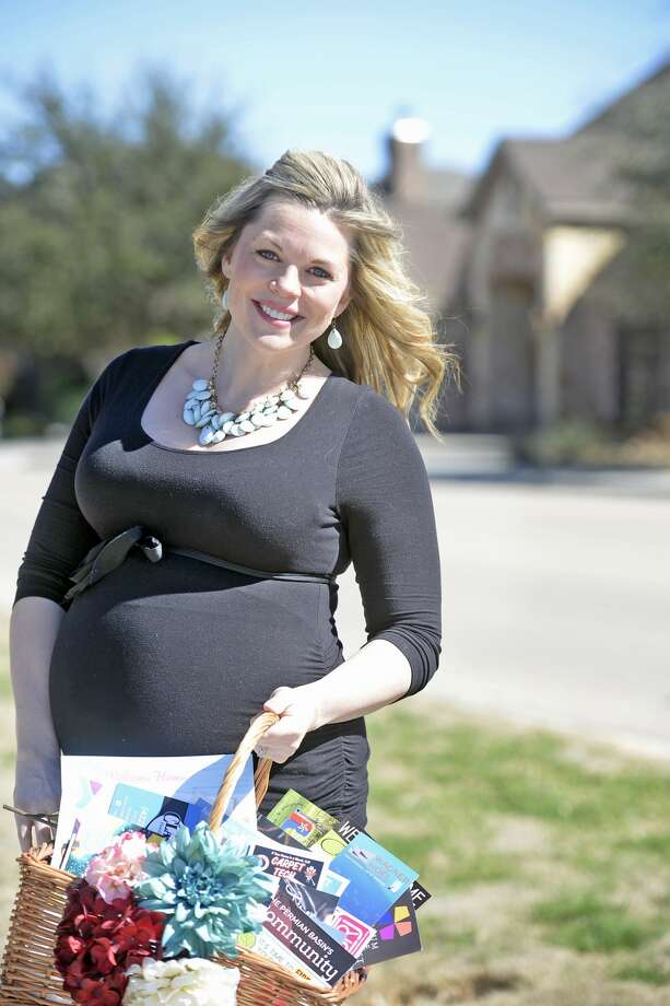 Christine Hager, pregnant with her second child Greyson, poses Feb. 24 with a gift basket she gives to new homeowners in the Woodland Park neighborhood. Hager owns Welcome Home Permian Basin, a new homeowner greeting service. Photo: James Durbin