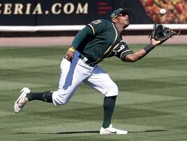 Oakland Athletics' Khris Davis makes a catch off a flyout hit by San Diego Padres' Carlos Asuaje during the third inning of a spring training baseball game, Saturday, March 18, 2017, in Mesa, Ariz. (AP Photo/Matt York)