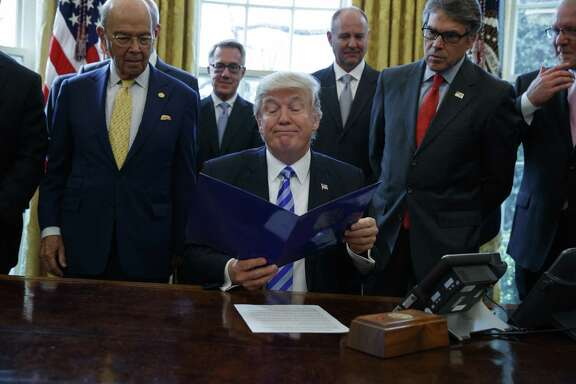 President Donald Trump, flanked by Commerce Secretary Wilbur Ross and Energy Secretary Rick Perry, is seen Friday in the Oval Office, where he announced the approval of a permit to build the Keystone XL pipeline, clearing the way for the $8 billion project.