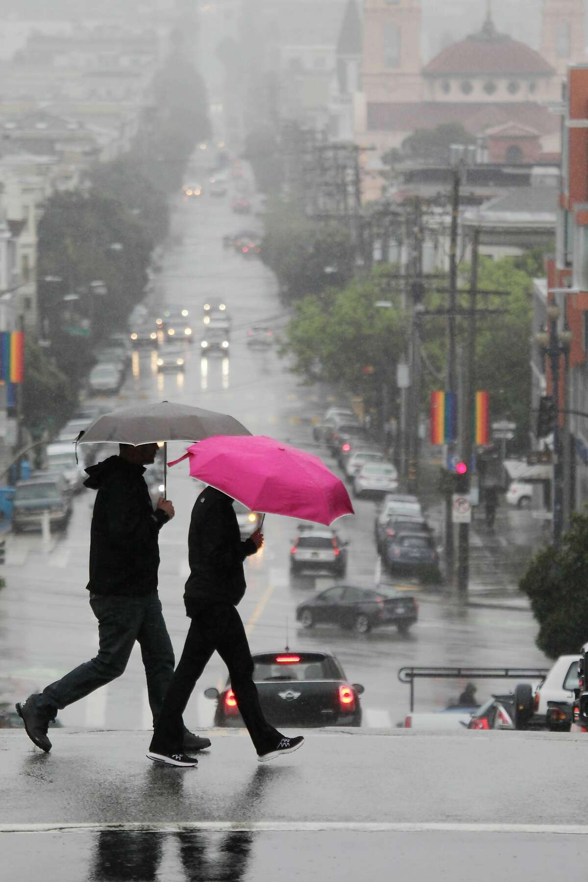 Pedestrians cross 16th Street under their umbrellas in the rain on Friday, March 24, 2017 in San Francisco, Calif.