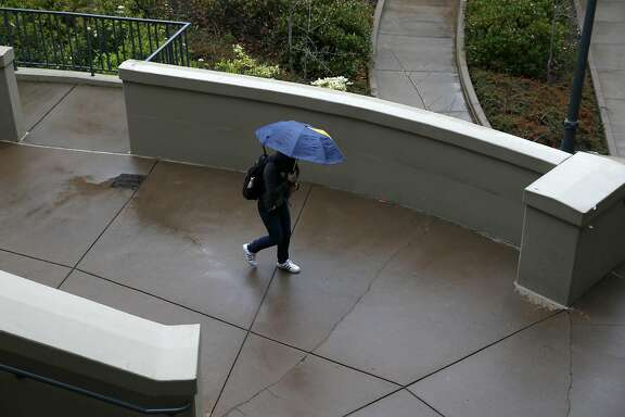 A student walks through the Haas School of Business in a rainstorm at UC Berkeley on Friday, March 24, 2017.