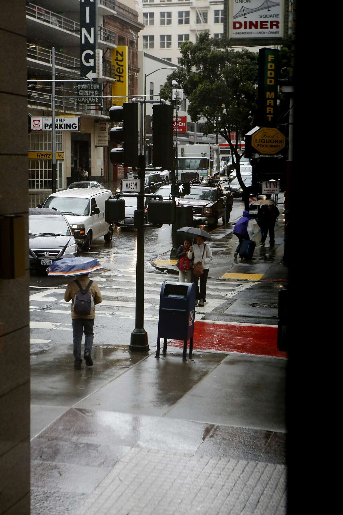 People walk through the rain in downtown San Francisco on Friday, March 24, 2017, in San Francisco, Calif.