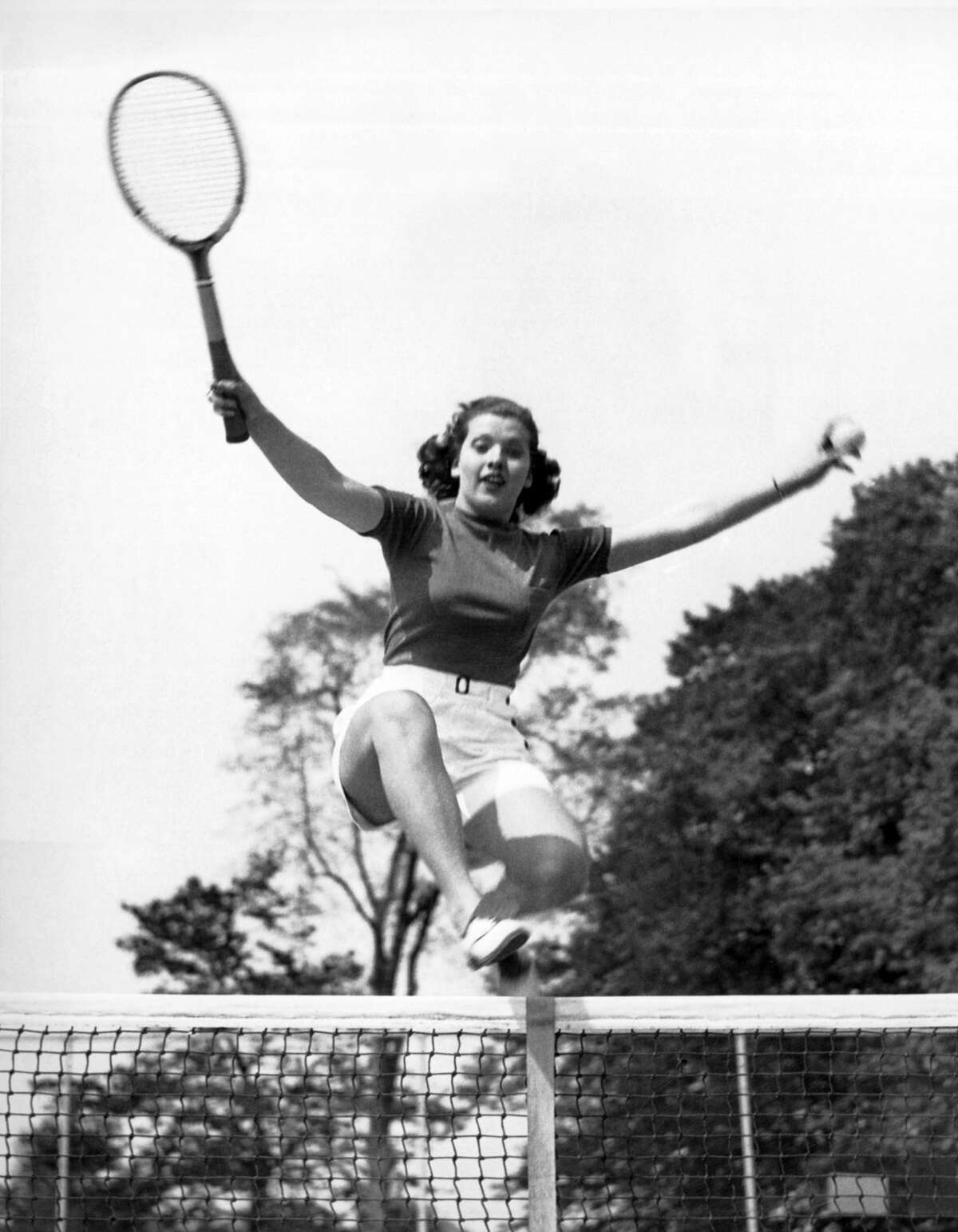 The 18 year old woman leaping over the tennis net was named 'Typical American Girl Athlete' by the Athletic Committee of the Longshore Club in Westport, Westport, Connecticut, May 23, 1936. (Photo by Underwood Archives/Getty Images)
