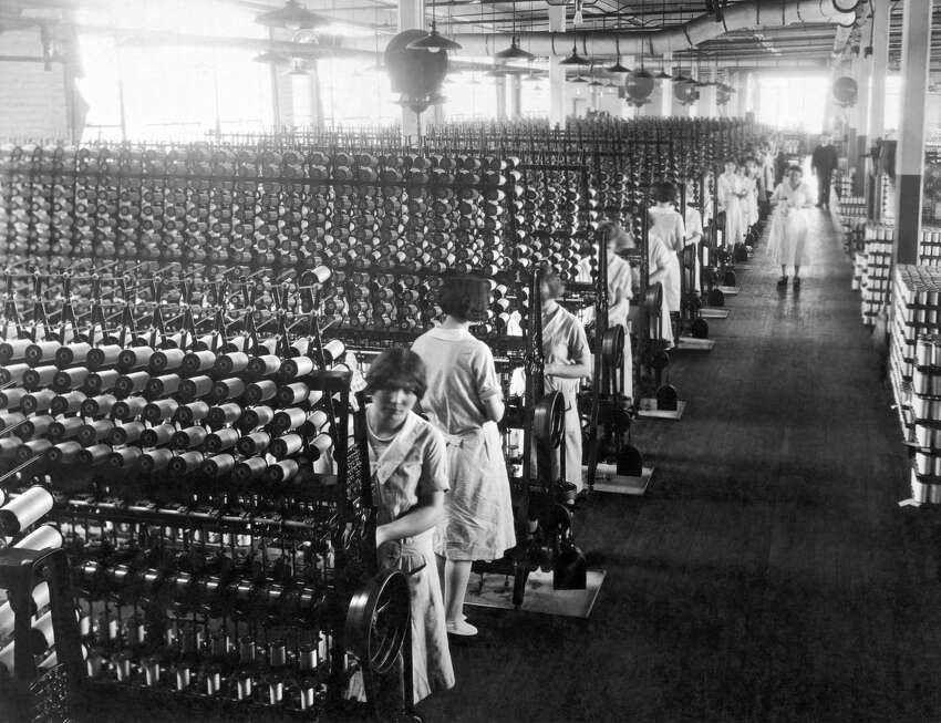 Women working at silk winding machines that will be used in the manufacturing of ladies hosiery, Connecticut, circa 1921. Photo by Underwood Archives/Getty Images