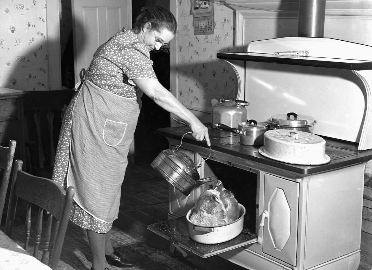 Mrs T. M. Crouch pours water over her twenty pound turkey on Thanksgiving day, 1940. Ledyard, Connecticut. (Photo by © CORBIS/Corbis via Getty Images)