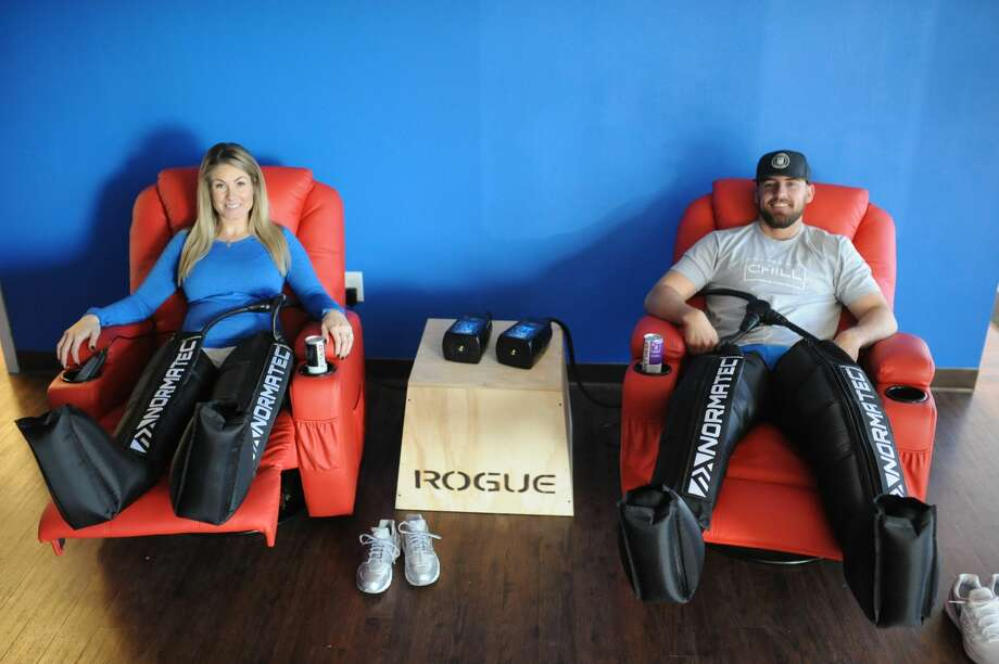 Amber and Tucker Schneemann, owners of Cryo Life, show off compression therapy treatments on Feb. 24 at their business that specializes in cryotherapy and compression therapy. Photo: James Durbin