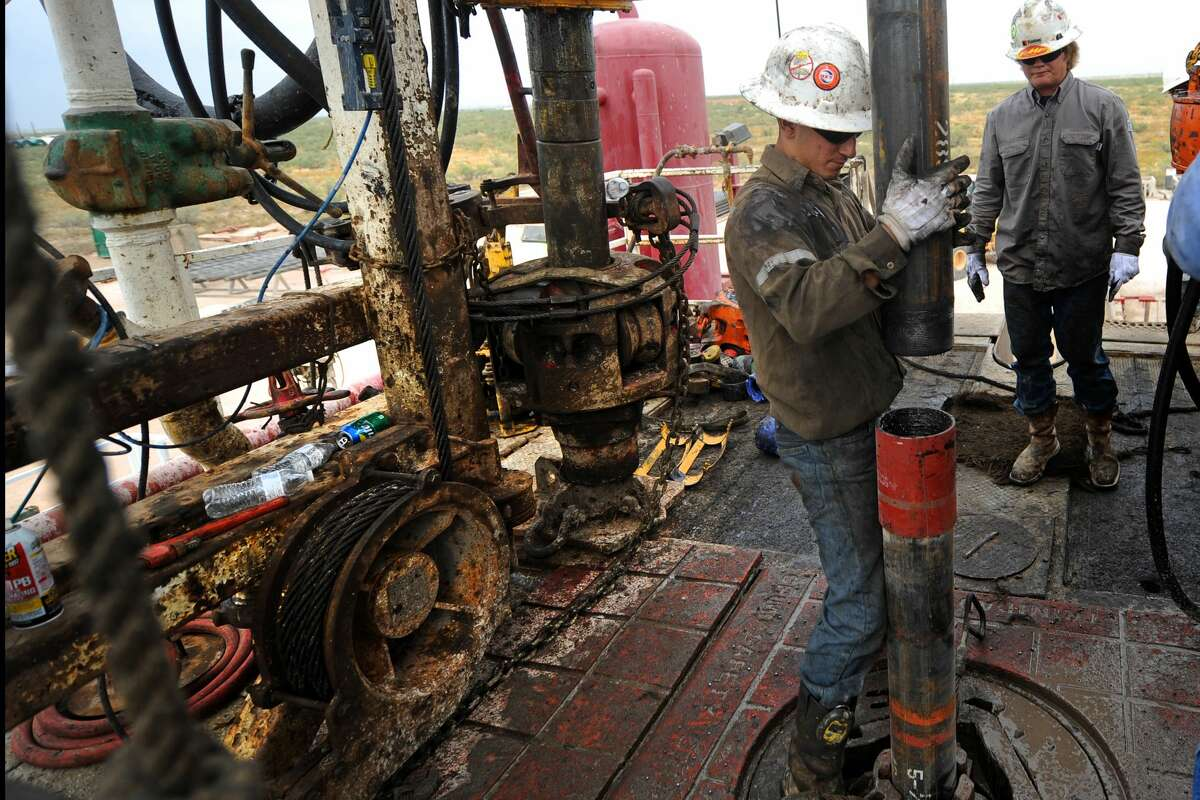 Noe Olvera connects a section of casing on the floor of Trinidad Rig 433 on Nov. 2, 2016, in Midland County.