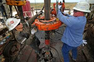 Noe Olvera, left, and Kevin Giddings, right, add a section of casing down a vertical well on the floor of Trinidad Rig 433 on Nov. 2, 2016, in Midland County.
