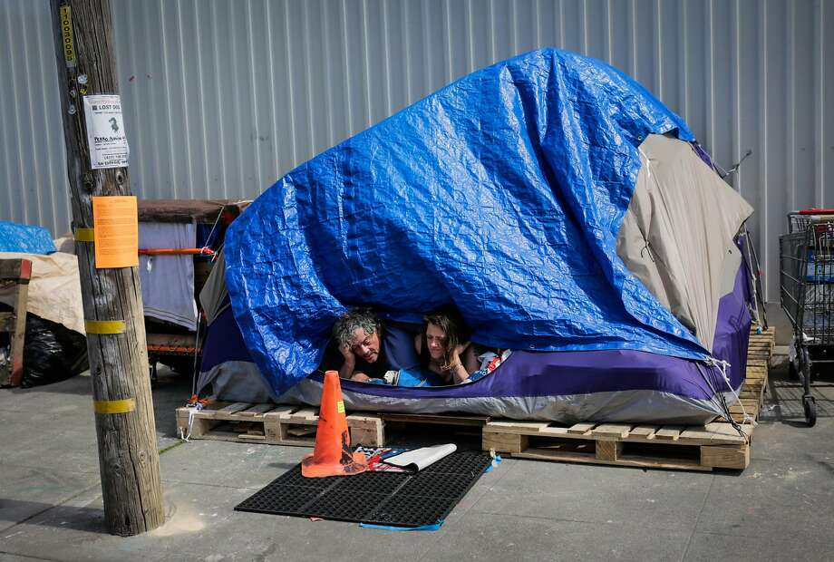 (l-r) Homeless couple Papa Smurf and his girlfriend Dawn Perry look out of their tent in the Design District in San Francisco, California, on Thursday, March 23, 2017. Photo: Gabrielle Lurie, The Chronicle