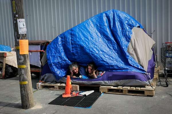 (l-r) Homeless couple Papa Smurf and his girlfriend Dawn Perry look out of their tent in the Design District in San Francisco, California, on Thursday, March 23, 2017.