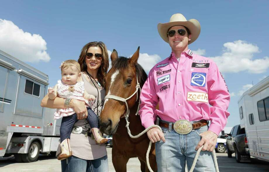 Tyson Durfey, Shea Fisher-Durfey, and their 6-month-old daughter Praise Royal Durfey, posed with Tyson's horse Nikko on Wednesday, as Tyson prepared to compete. Photo: Melissa Phillip, Houston Chronicle / © 2017 Houston Chronicle