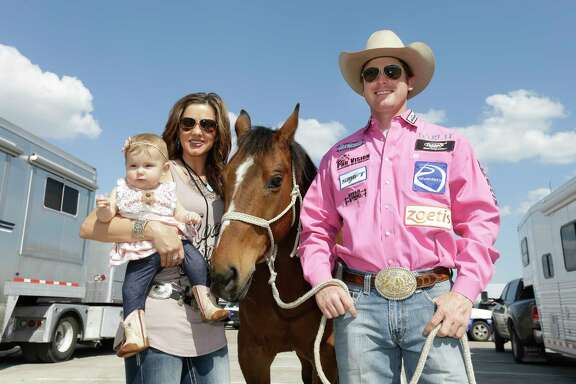 Tie-down roper Tyson Durfey with his wife, Shea Fisher-Durfey, and their 6-month-old daughter, Praise Royal Durfey, pose with his horse named Nikko before Tyson prepares to compete at Houston Livestock Show and Rodeo Wednesday, March 22, 2017, in Houston. He and his wife met at the Houston Rodeo in 2010.