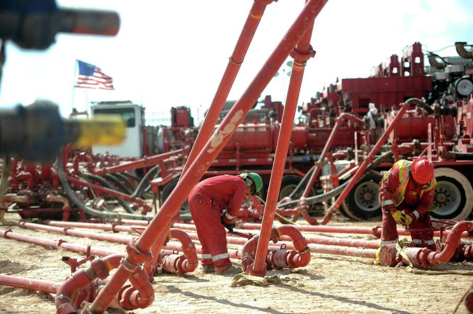 Halliburton employees work on high-pressure pipes supplying a fracking site near Stanton. Halliburton Chairman and CEO Dave Lesar said the company is spending more money now to protect market share and ensure stronger profits in the future. One of the moves it's making is adding 2,000 U.S. jobs. Photo: James Durbin /Midland Reporter-Telegram / © 2016 Midland Reporter Telegram. All Rights Reserved.