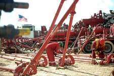 Halliburton employees work on high-pressure pipes supplying a fracking site near Stanton. Halliburton Chairman and CEO Dave Lesar said the company is spending more money now to protect market share and ensure stronger profits in the future. One of the moves it's making is adding 2,000 U.S. jobs.