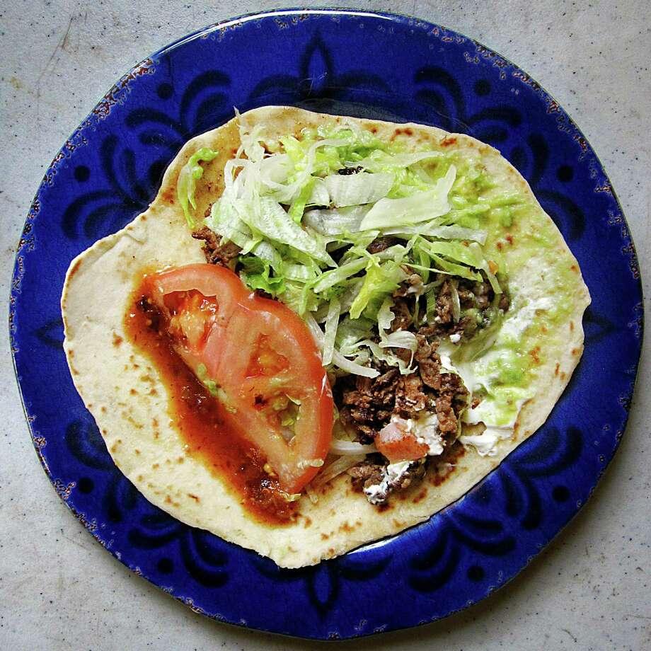 Taco Arandas taco with carne aside, lettuce, tomato, sour cream and guacamole on a handmade flour tortilla from Taquería Arandas on West Military Drive. Photo: Mike Sutter /San Antonio Express-News