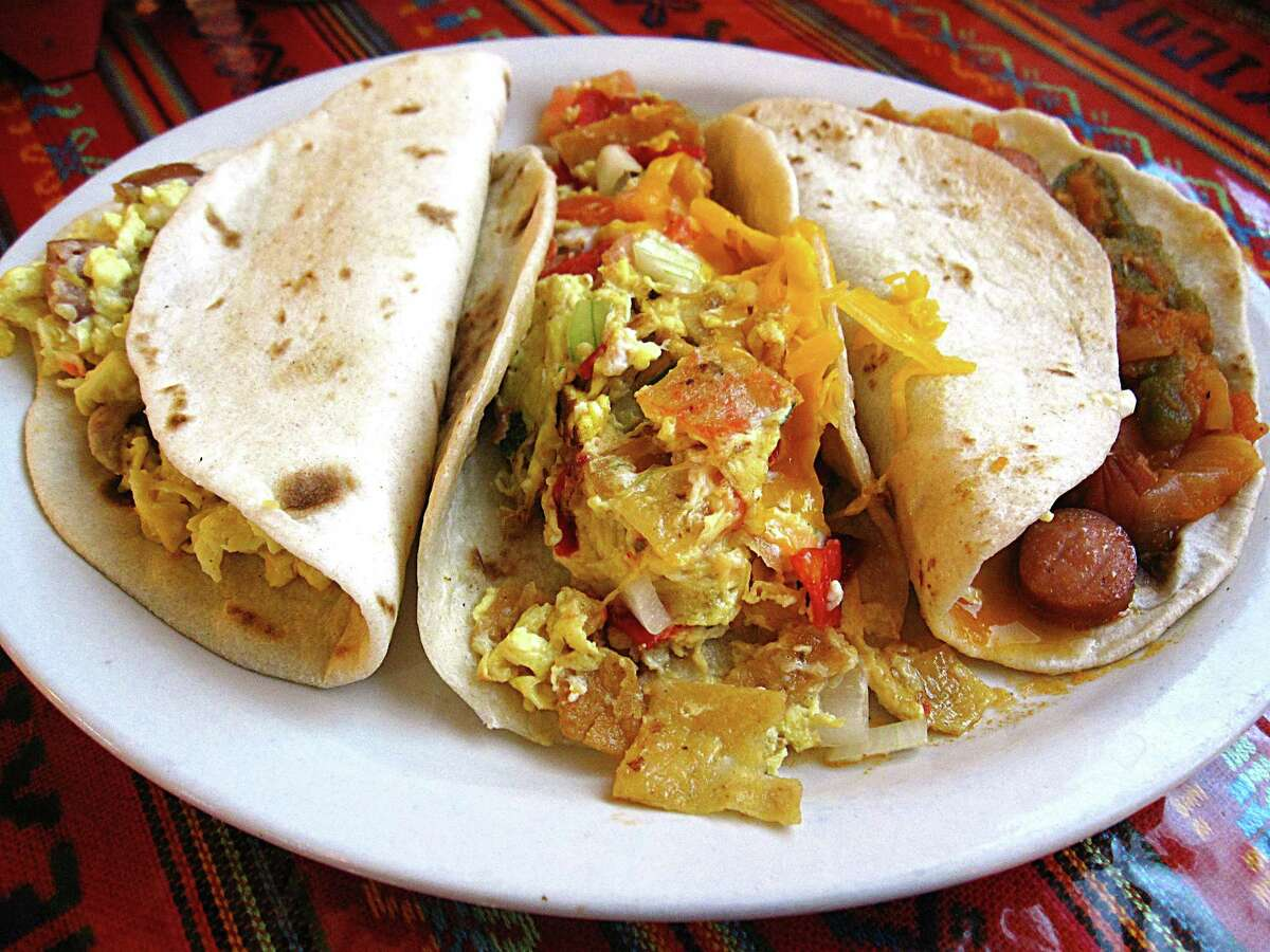A trio of breakfast tacos on handmade flour tortillas, From left: Country sausage and egg, chilaquiles and weenies in salsa. From Los Campos Dos Hermanos.