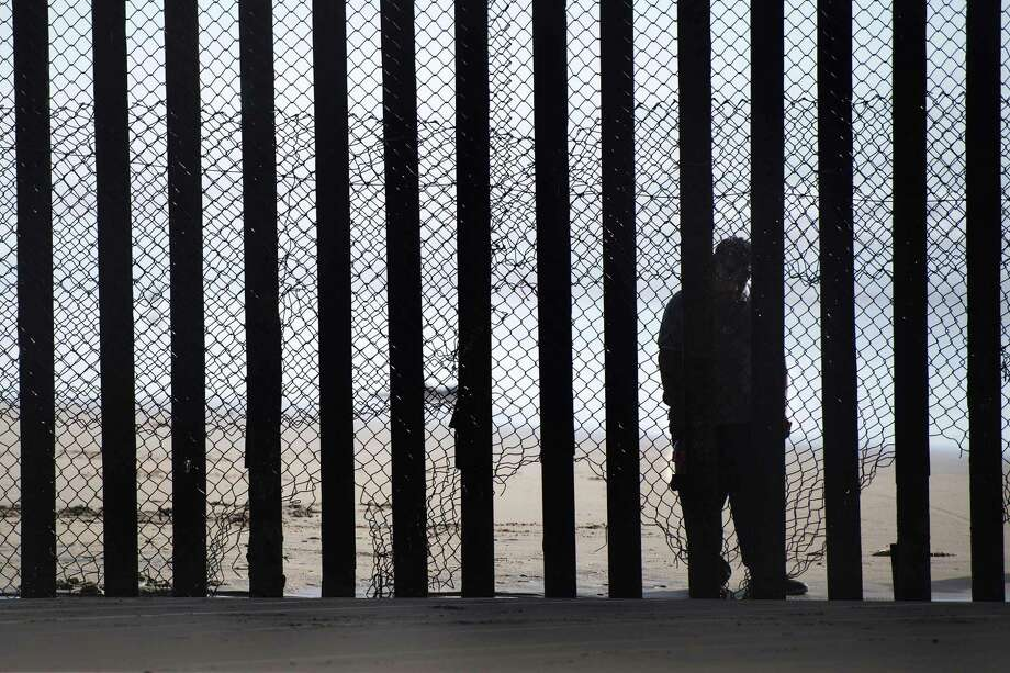 A man standing on the Mexico side of a border fence separating the beaches at Border Field State Park, in San Diego, California in February. A pragmatic immigration policy would find a way to let more workers in because a declining birth rate in the U.S. means fewer workers. Photo: JIM WATSON /AFP /Getty Images / AFP or licensors