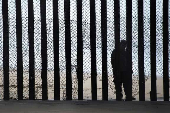 A man standing on the Mexico side of a border fence separating the beaches at Border Field State Park, in San Diego, California in February. A pragmatic immigration policy would find a way to let more workers in because a declining birth rate in the U.S. means fewer workers.