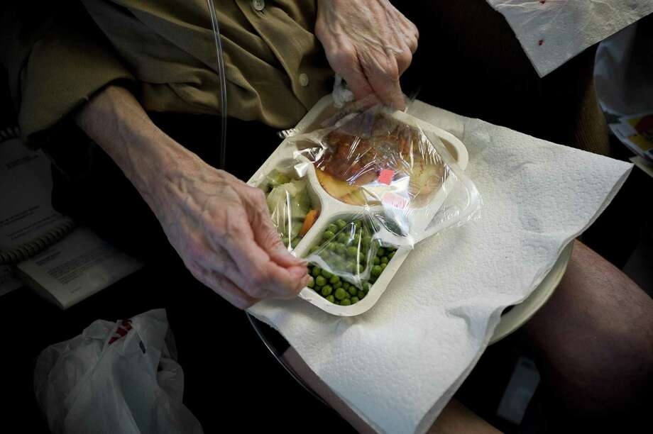 A disabled pilot opens a prepared meal at his home in Portland, Ore., July 12, 2010. Meals on Wheels has been the subject of many peer-reviewed studies in the medical literature, most of which show that the program improves the quality of people's diet, increases their nutrient intake and reduces their food insecurity and nutritional risk. Photo: LEAH NASH /NYT / NYTNS