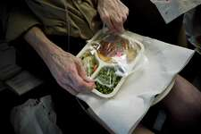 A disabled pilot opens a prepared meal at his home in Portland, Ore., July 12, 2010. Meals on Wheels has been the subject of many peer-reviewed studies in the medical literature, most of which show that the program improves the quality of people's diet, increases their nutrient intake and reduces their food insecurity and nutritional risk.