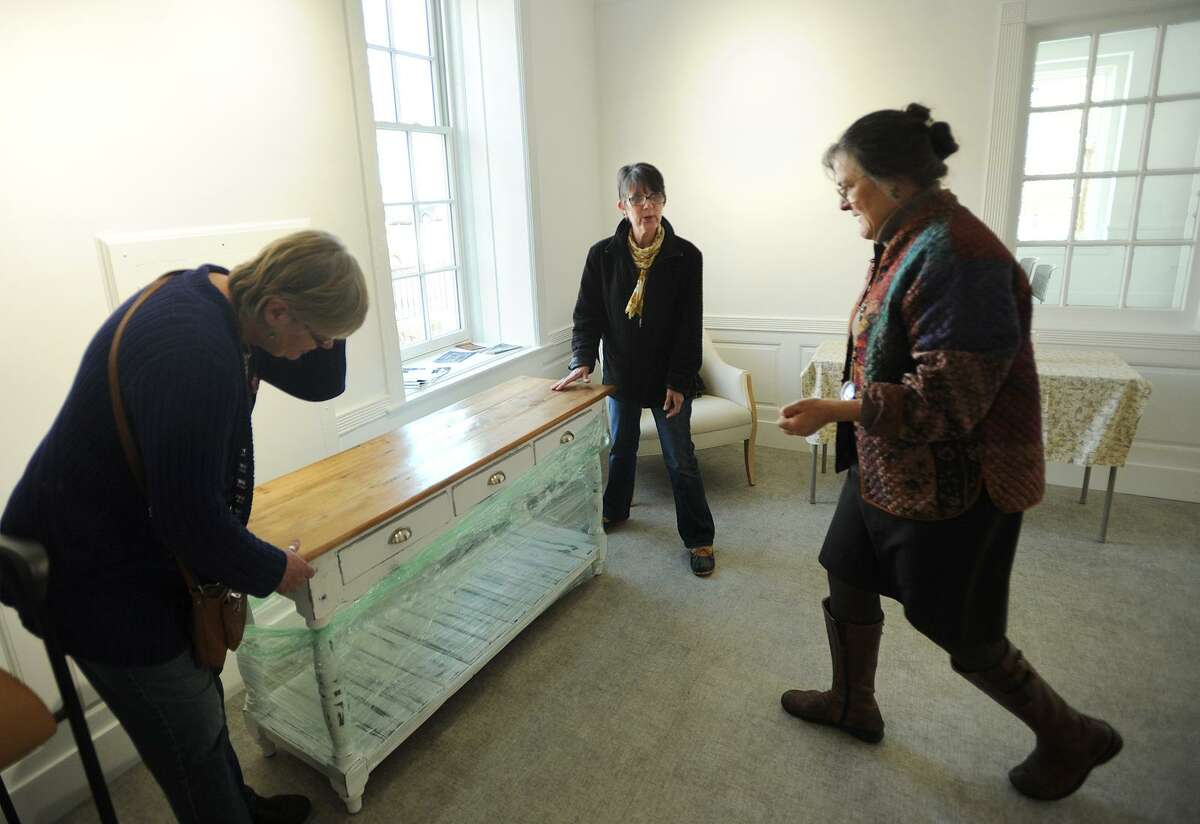 From left; Artists Susan Murray, of Monroe, and Tracey Anderson-Kollar, of Bridgeport, place a piece of furniture under the guidance of Executive Director Suzanne Kachmar at the new City Lights Gallery space at 265 Golden Hill Street in Bridgeport, Conn. on Tuesday, March 21, 2016. The new space will open to the public with a ribbon cutting ceremony on April 6.