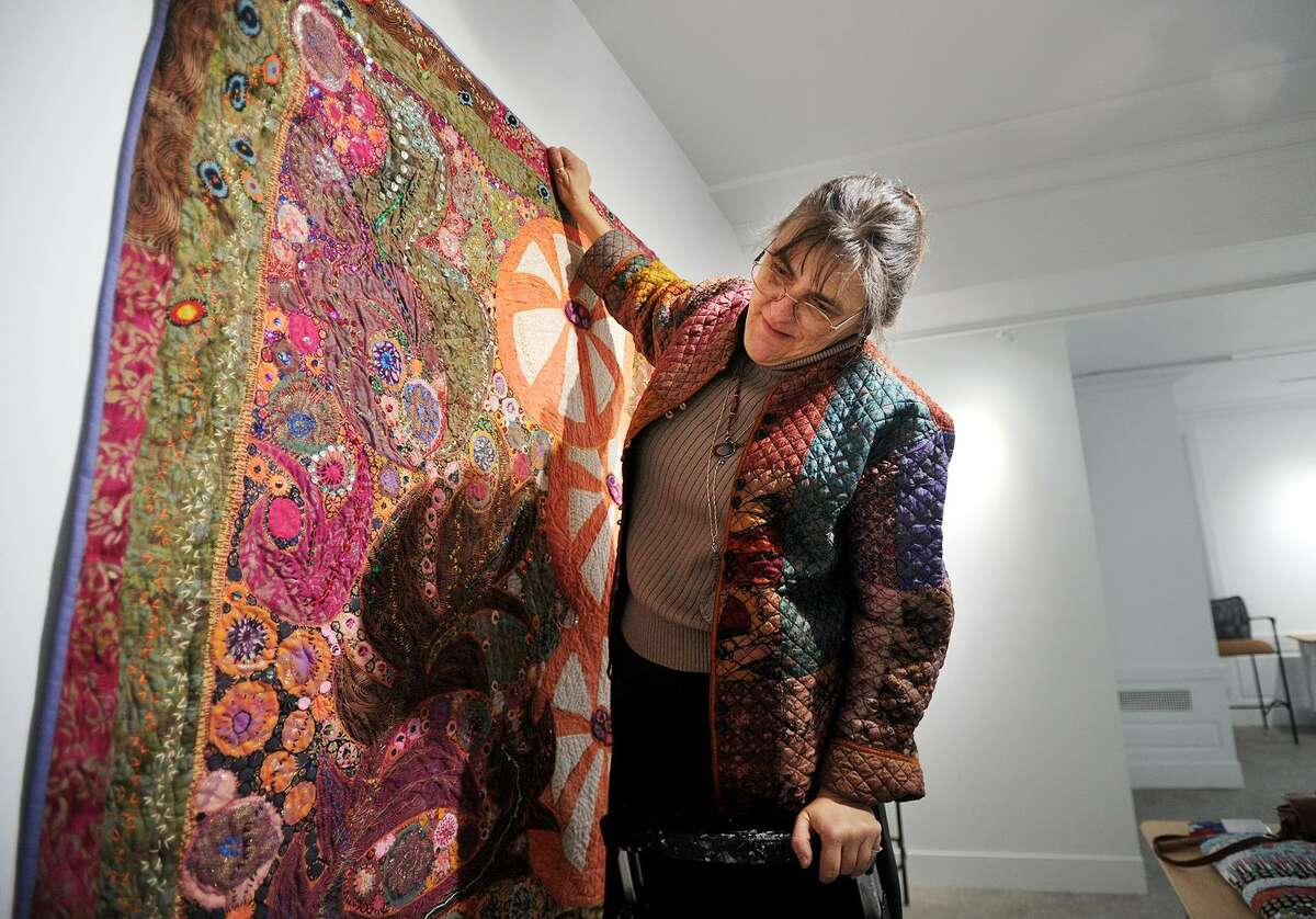 Executive Director Suzanne Kachmar hangs a quilt tapestry on one of the walls of the new City Lights Gallery space at 265 Golden Hill Street in Bridgeport, Conn. on Tuesday, March 21, 2016. The new space will open to the public with a ribbon cutting ceremony on April 6.