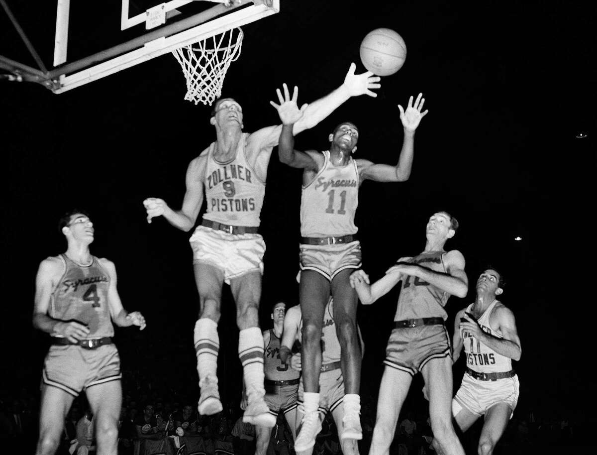 In this April 1955 file photo, Fort Wayne's Mel Hutchins (9) and Syracuse's Earl Lloyd (11) reach for the ball during an NBA game in Indianapolis. Lloyd, the first black player in NBA history, died Feb. 26, 2015, at age 86. Lloyd made his NBA debut in 1950 for the Washington Capitals, just before fellow black players Sweetwater Clifton and Chuck Cooper played their first games.
