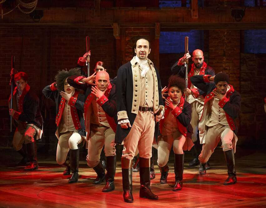 FILE - In this file photo released by The Public Theater, Lin-Manuel Miranda, foreground, performs with members of the cast of the musical