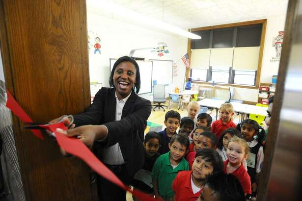 FILE — Assistant Superintendent Dr. Tamu Lucero cuts the ribbon to one of the classrooms at the New School, on Strawberry Hill Ave. in Stamford, Conn., on Thursday, September 1, 2016.