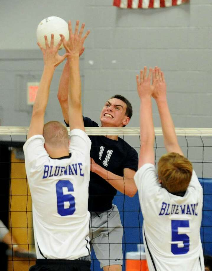 Staples' #11 Tom Prenderville, center, spikes the ball as Darien's #6 Caldder Billhardt, left, and teammate #5 Tommy Nicholls, try to block, during FCIAC Boys Volleyball Tournament action in Fairfield, Conn. on Friday May 28, 2010. Photo: Christian Abraham / Connecticut Post