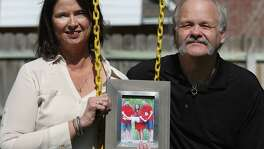 Janis and Matt Stewart hold a frame of the family of her daughter, Sunday Stewart Rowan, on a swing set in their backyard Friday, March 3, 2017, in College Station. Rowan and her husband Matt Rowan, right in the photo, died in the hot air  balloon crash in Lockhart in 2016, and left behind a son, Jett Sunday Jones. On the left in the photo is Jett's father, Brent Jones.