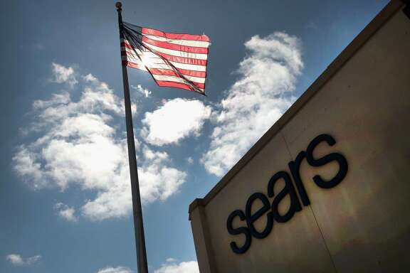 "A flag flies outside a Sears store in Schaumburg, Ill., after parent company Sears Holdings said in March there is ""substantial doubt"" about the company's financial viability (Photo by Scott Olson/Getty Images)"