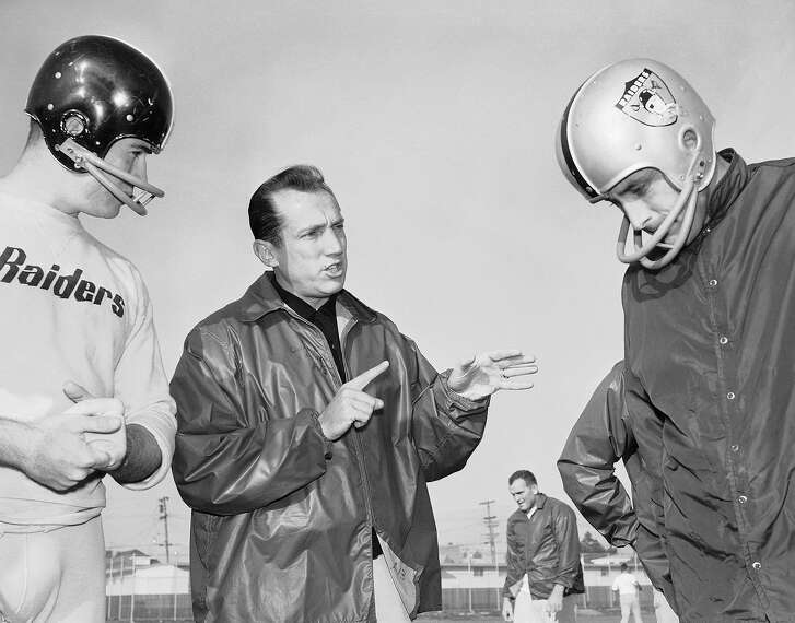 In this Dec. 18, 1963 file photo, Al Davis, center, head coach of the American Football League's Oakland Raiders, talks with players at the team's home practice field in Oakland, Calif. Davis, the Hall of Fame owner of the Oakland Raiders known for his rebellious spirit, has died. The team announced his death at age 82 on Saturday, Oct. 8, 2011.