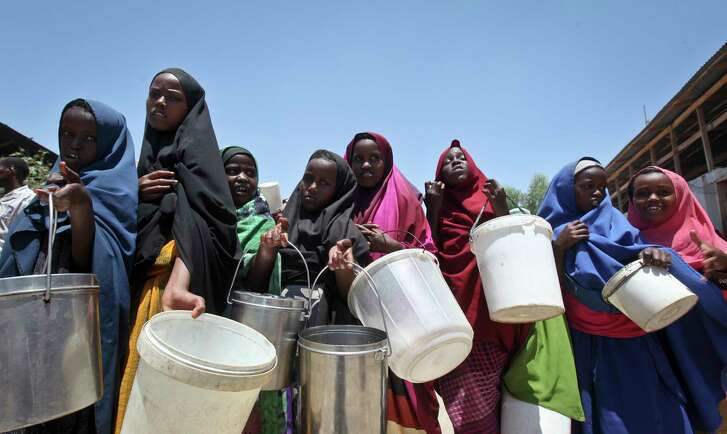 Displaced Somali girls who fled the drought in southern Somalia stand in a queue to receive food handouts at a feeding center in a camp in Mogadishu, Somalia. (AP Photo/Farah Abdi Warsameh, File)