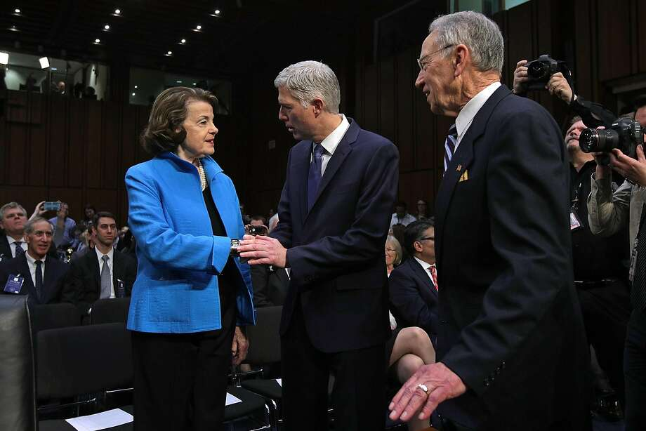 Judge Neil Gorsuch (center) greets Senate Judiciary Committee ranking member Sen. Dianne Feinstein, D-Calif., and Chairman Charles Grassley, R-Iowa, for the first day of his Supreme Court confirmation hearing. Photo: Alex Wong, Getty Images