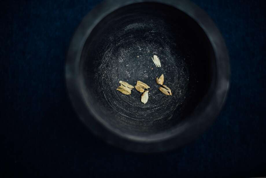 Crack the green cardamom pods using a mortar and pestle; discard the green pod and crush the seeds. Photo: Nik Sharma