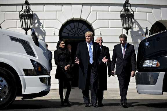 U.S. President Donald Trump, center, speaks while meeting Chris Spear, president of the American Trucking Associations (ATA), right, during an event to meet truckers and truck industry chief executive officers with U.S. Vice President Mike Pence on the South Lawn of the White House in Washington, D.C., U.S., on Thursday, March 23, 2017. House leaders delayed a scheduled vote on their embattled health-care bill as conservatives mulled a deal proposed by the Trump administration aimed at winning Republican holdouts support. Photographer: Andrew Harrer/Bloomberg