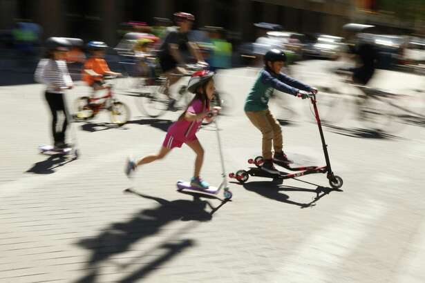 Kids on skateboard join others during the 10th s'colov'a  in downtown San Antonio. This free event turns city streets into a safe place for people to exercise and play when they become car-free from 11 a.m. to 3 p.m on Sunday,April 3, 2016.  Slow shitter speed with pan gives the photo the effect it has.